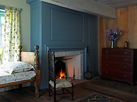 A child's single bed has been placed under the window beside a welcome fire in this guest bedroom