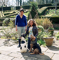 Rosie Pearson and her daughter pictured with the dogs of the house on the stone-flagged terrace next to the parterre on the garden side of the house