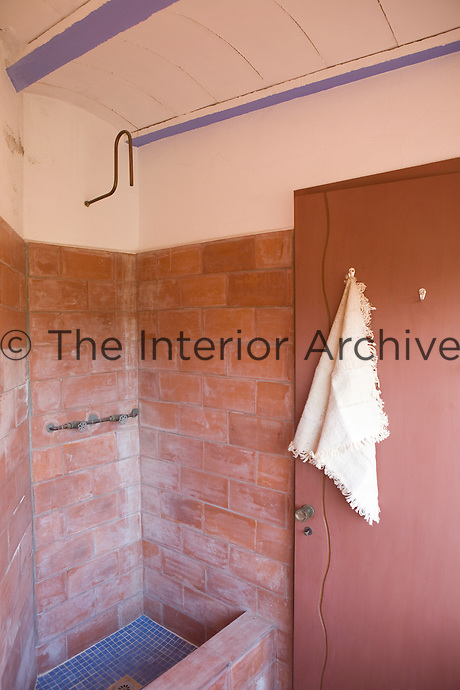 A simple terracotta tiled shower in a rustic bathroom.