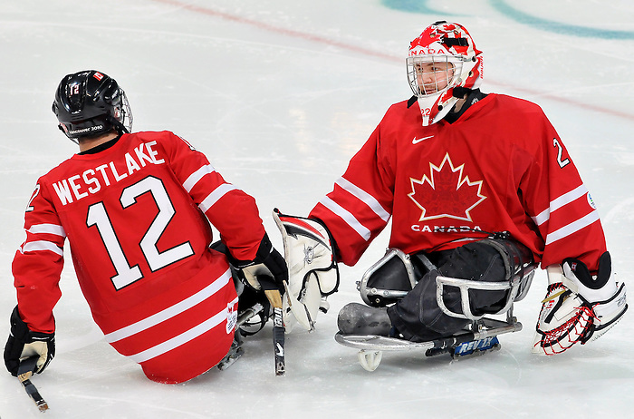 Benoit St-Amand (22) congradulates Greg Westlake (12) after a goal during 2010 Paralympic Games sledge hockey action at UBC Thunderbird Arena in Vancouver. Credit: CPC/HC/Matthew Manor.