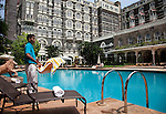 MUMBAI, INDIA - SEPTEMBER 27, 2010: A waiter shakes a towel out by the pool at the Taj Mahal Palace and Tower Hotel in Mumbai. The hotel has re-opened after the terror attacks of 2008 destroyed much of the heritage wing. The wing has been renovated and the hotel is once again the shining jewel of Mumbai. pic Graham Crouch