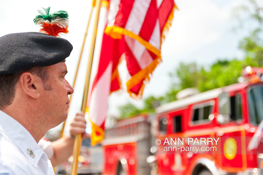 Fire Department Emerald Society member watching fire engines in Merrick Memorial Day Parade on Monday, May 28, 2012, on Long Island, New York, USA. America's war heroes are honored on this National Holiday.