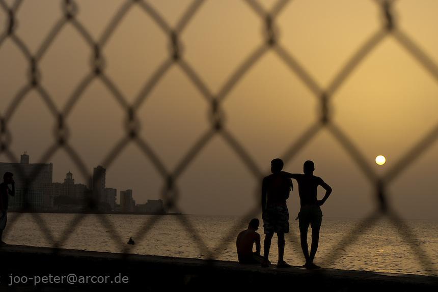 friends watching sunset at Malecon, Havana, Cuba