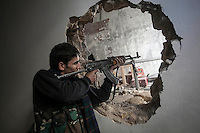 In this Sunday, Dec. 02, 2012 photo, a rebel fighter aims on his enemy's positon from a hole in the Amarya district after the rebel fighters took control of the area over the Syrian army during heavy fighting in Aleppo, the Syrian's largest city. (AP Photo/Narciso Contreras)