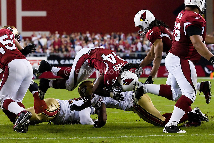 Nov 10, 2008; Glendale, AZ, USA; Arizona Cardinals running back Tim Hightower (34) dives over two San Francisco 49ers defenders in the third quarter of a Monday Night Football game at University of Phoenix Stadium.  The Cardinals won 29-24.