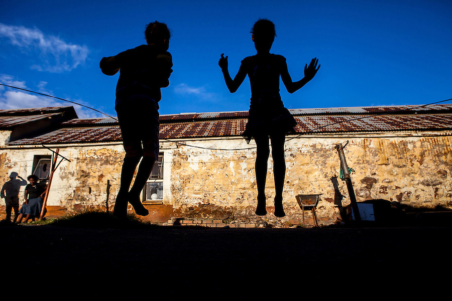I photographed these young girls skipping at an abandoned goldmine hostel that is home to them and many poor families on the outskirts of Johannesburg, South Africa. In the previous few weeks before this photograph was taken, the area had been robbed of all its cable (stolen for its copper) so no one had electricity anymore. Ironically, the girls were using the casing from stolen cable to skip with. Violence and sexual violence against girls and women in South Africa is widely recognized to have reached levels among the highest in the world and is particularly high in the impoverished shanty towns and squatter camps like this abandoned hostel.