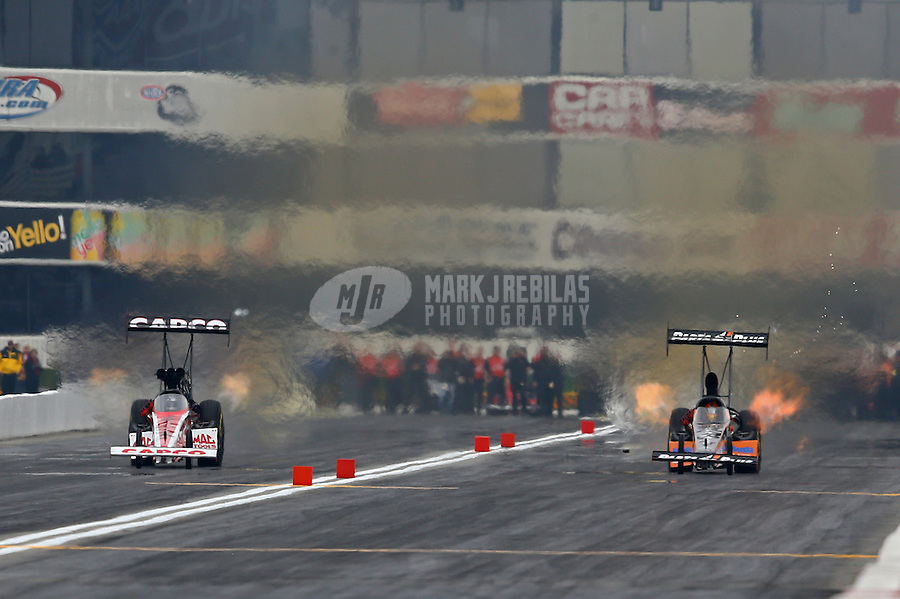 Feb 9, 2014; Pomona, CA, USA; NHRA top fuel dragster driver Steve Torrence (left) races alongside Clay Millican during the Winternationals at Auto Club Raceway at Pomona. Mandatory Credit: Mark J. Rebilas-