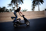 "Baghdad, Iraq  : Fri 15th Oct 2010 :..A young teen performs on his scooter as part of an unofficial bike show  in Baghdad's Jadriya district. An underground youth scene has developed around motorbike culture in the Iraqi capital. .Every week Iraqi teens and young men arrive with their motorcycles, scooters and bicycles at selected street locations to  perform tricks and socialize as part of a burgeoning Baghdadi bike culture. .From ""Yesterday's War, Today's Iraq,"" an ongoing series documenting Iraq and Iraqis as US forces withdraw from the country and media interest wanes. ."