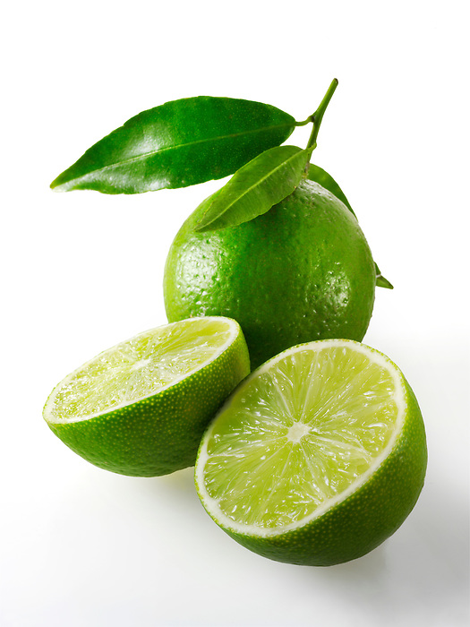 Fresh whole and cut lime fruit with leaves