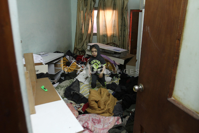 A Palestinian boy stands in his room after his house was searched by Israeli forces on June 17, 2014 at the Balata refugee camp, close to the northern West Bank city of Nablus. Large numbers of Israeli soldiers raided the northern West Bank city of Nablus and its surroundings early 17 June 2014 in the search of three teenagers, three teenagers - Eyal Yifrah, 19, Gilad Shaar, 16, and Naftali Frenkel, 16 - missing since 08 JUne 2014, near the Gush Etzion settlement bloc, north of Hebron. Photo by Nedal Eshtayah