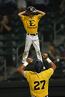 Right fielder Aaron Maher (27) of ETSU tosses 10-year-old Gehrig Skole, son of head coach Tony Skole, into the air after scoring a run in a game against Furman at the Southern Conference Baseball Championship on Saturday, May 27, 2017, at Fluor Field at the West End in Greenville, South Carolina. Furman won, 8-6. (Tom Priddy/Four Seam Images)
