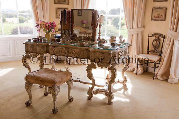 An ornate Italian-style dressing table in the master bedroom is matched with a stool upholstered in its original silk
