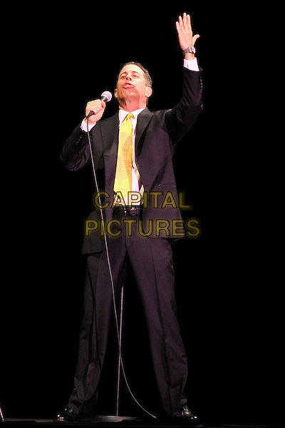 Jerry Seinfeld .performing live at the O2 Arena, London, England, UK, June 3rd 2011..full length on stage show stand-up comedian grey gray black suit tie microphone hand arm raised up .CAP/MAR.© Martin Harris/Capital Pictures.