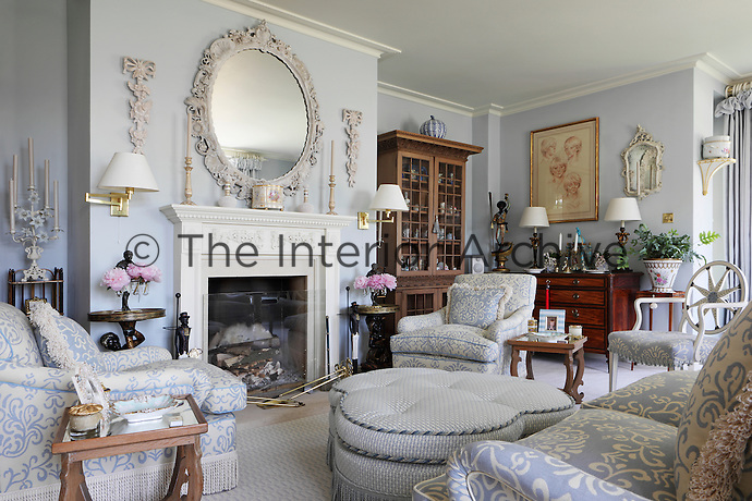 A pale blue living room furnished with cosy blue and white armchairs