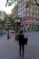 Tourist photographing the Gastown Steam Clock in the historical Gastown district, Vancouver, BC, Canada
