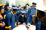 WATERBURY, CT-062117JS17- Kennedy High School graduates look for their diplomas on tables in the gym following graduation ceremonies Wednesday at Kennedy High School in Waterbury.  Jim Shannon Republican-American