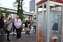 October 28, 2011, Osaka, Japan - People get curious enough to take pictures of what looks like an ordinary public pay phone booth filled with water for gold fish to swim freely inside at Nakanoshima Park in Osaka, western Japan, on Friday, October 28, 2011. The phone booth-turned-aquarium is a form of public art, aiming at raising awareness among people about the way the gold fish are mass-produced and consumed. (Photo by Akihiro Sugimoto/AFLO) [1080] -mis-