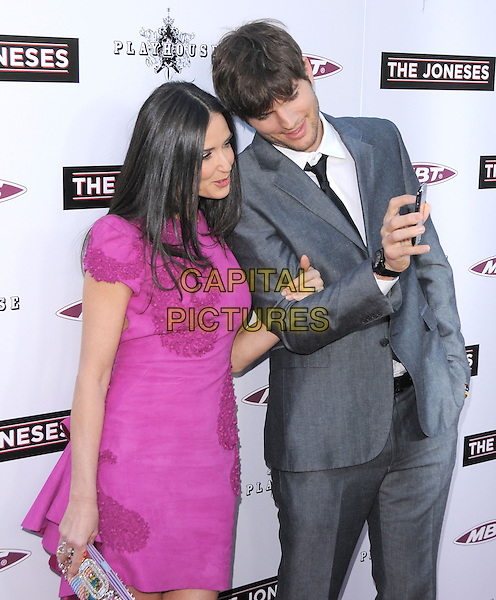 "DEMI MOORE & ASHTON KUTCHER .at the L.A. Premiere of ""The Joneses"" held at The Arclight Theatre in Hollywood, California, USA, .April 8th, 2010..arrivals half length pink purple embroidered textured dress married couple husband wife clutch bag grey gray suit black tie white shirt looking at mobile cell phone .CAP/RKE/DVS.©DVS/RockinExposures/Capital Pictures."