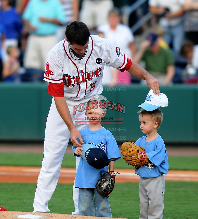 August 13, 2009: RHP Caleb Clay (5) of the Greenville Drive shows a pair of young ballplayers how to take off their hats during the National Anthem before a game at Fluor Field at the West End in Greenville, S.C. Photo by: Tom Priddy/Four Seam Images