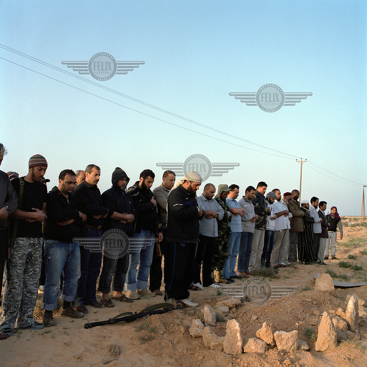 Rebels pray for several bodies found in shallow graves on the road near Brega. On 17 February 2011 Libya saw the beginnings of a revolution against the 41 year regime of Col Muammar Gaddafi.