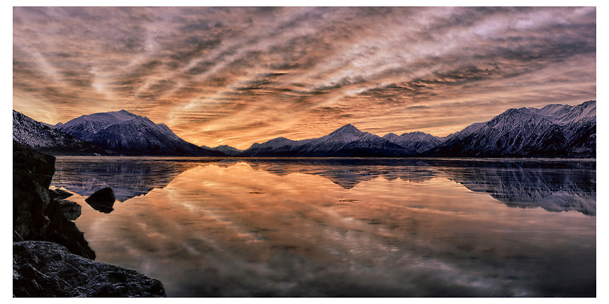 Panorama of the high tide reflection as the sun rises over the Kenai Mountains boardering the Turnagain Arm of Cook Inlet, Alaska.