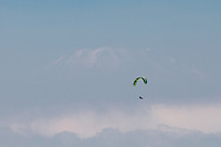 A parapenter fies in front of a cloudy Mount Fuji above Matsuda, Kanagawa, Japan. Saturday January 16th 2016