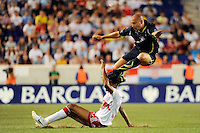 Alan Hutton (2) of Tottenham Hotspur F. C. jumps over the tackle of Roy Miller (7) of the New York Red Bulls. Tottenham Hotspur F. C. defeated the New York Red Bulls 2-1 during a Barclays New York Challenge match at Red Bull Arena in Harrison, NJ, on July 22, 2010.