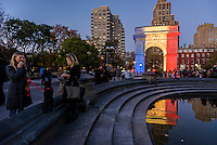 New York, NY - 15 November 2015 NYC  The arch in Washington Square Park alights up in solidarity with Paris.  Beneath the arch is a candlelight shrineto commemorate the victims of the 13 November Paris terror attacks.