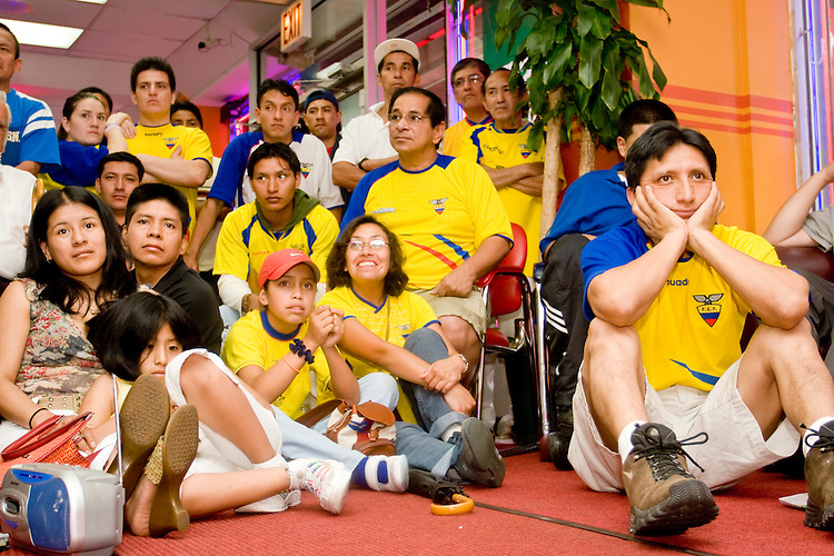 Ecuador fans watch their team play England in a World Cup match on June 25, 2006 at Delgado Travel, a travel agency in New York City.<br /> <br /> The World Cup, held every four years in different locales, is the world's pre-eminent sports tournament in the world's most popular sport, soccer (or football, as most of the world calls it).  Qualification for the World Cup is open to any country with a national team accredited by FIFA, world soccer's governing body. The first World Cup, organized by FIFA in response to the popularity of the first Olympic Games' soccer tournaments, was held in 1930 in Uruguay and was participated in by 13 nations.    <br /> <br /> As of 2010 there are 208 such teams.  The final field of the World Cup is narrowed down to 32 national teams in the three years preceding the tournament, with each region of the world allotted a specific number of spots.  <br /> <br /> The World Cup is the most widely regularly watched event in the world, with soccer teams being a source of national pride.  In most nations, the whole country is at a standstill when their team is playing in the tournament, everyone's eyes glued to their televisions or their ears to the radio, to see if their team will prevail.  While the United States in general is a conspicuous exception to the grip of World Cup fever there is one city that is a rather large exception to that rule.  In New York City, the most diverse city in a nation of immigrants, the melting pot that is America is on full display as fans of all nations gather in all possible venues to watch their teams and celebrate where they have come from.