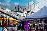 Children walk along a funhouse bridge as people walk through the carnival area during St. Peter's Fiesta in Gloucester, Massachusetts, USA.