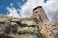 A hiker explores the historic fire lookout atop Harney Peak, the highest point east from the Black Hills to the Pyrenees Mountains in France.