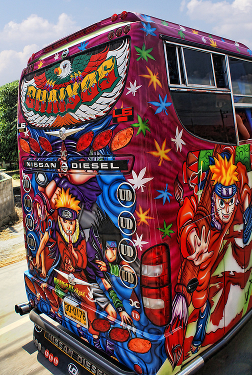 One of the many buses in Thailand decorated with the world-favorite, Japanese Animee characters. Surrounding the main character, Narato, are other characters all painted in bright, eyecatching colors of shades of red, blue, gold and green on a maroon background.