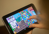 A woman plays the popular mobile game Candy Crush Saga on a tablet in New York on Wednesday, February 19, 2014. The maker of the wildly popular game, King Digital Entertainment, has filed for an Initial Public Offering. The game accounts for almost 80 percent of the company's revenue, achieving that from sales of add-ons and upgrades to the free game.  (© Richard B. Levine)
