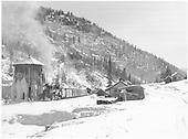 A snow clad panoramic view of leased D&amp;RGW #461 with a northbound freight taking water at Brown with leased D&amp;RGW #452 helping.<br /> RGS  Brown, CO  Taken by Richardson, Robert W. - 11/19/1951