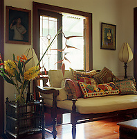 An Indian daybed is piled with colourful scatter cushions against double glazed doors which open on to the porch