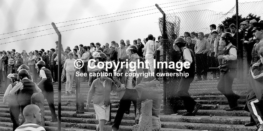 Husband leads his wife to safety as police in riot gear move in among football fans to keep the peace at a friendly pre-season match between  Cliftonville FC and visitors, Glasgow Celtic. 19840098d..Copyright Image from Victor Patterson, 54 Dorchester Park, Belfast, UK, BT9 6RJ..Tel: +44 28 9066 1296.Mob: +44 7802 353836.Voicemail +44 20 8816 7153.Skype: victorpattersonbelfast.Email: victor@victorpatterson.com.<br />