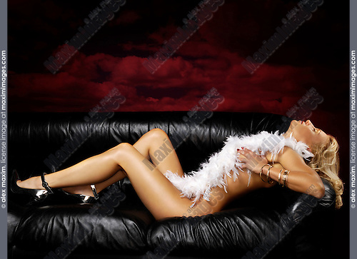 Beautiful naked woman with white feathers lying on black leather couch