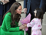 AUSTRALIA, Canberra : Britains Catherine, Duchess of Cambridge (L) receives flowers from three year old Wilhelmina Dreghorn during a visit to the National Portrait Gallery, Canberra on April 24, 2014. Britain's Prince William, his wife Kate and their son Prince George are on a three-week tour of New Zealand and Australia. AFP PHOTO / Mark GRAHAM