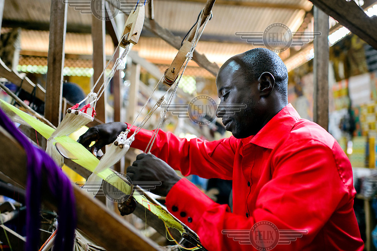 Master Weaver, Eric Kwarteng, crafting traditional Kente cloth at his loom in a weaving centre in the small town of Bonwire.