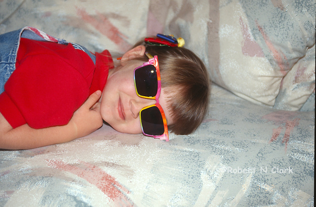 Girl on sofa wearing sunglasses