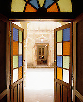A pair of simple wooden doors with coloured glass panes and fanlight open onto a sunlit courtyard