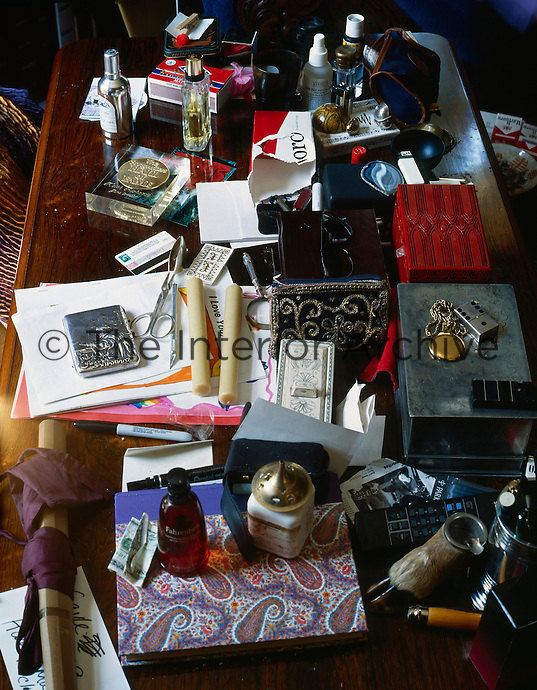 Personal effects and assorted objects are scattered in chaotic fashion across this table