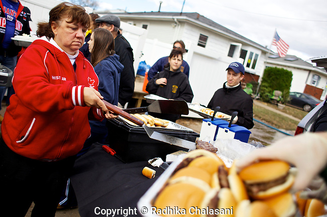 MIDLAND BEACH-NEW YORK-NOVEMBER 03:  Evelyn Rogers and and other members of the NorthShore Long Island Rotary Club cook burgers and hot dogs for residents and volunteers on Greeley Avenue in Midland Beach in the Staten Island borough of New York City after Hurricane Sandy November 3, 2012. Rogers owns a catering company on Staten Island. Staten Island saw an influx of volunteers today as it tries to recover from the devastating storm that left 19 dead on the island.