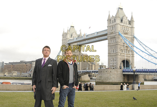 """SHANE RICHIE & LEX SHRAPNEL  .The """"Minder"""" 80's sitcom remake photocall, Potters Field, London, England..January 13th, 2009.half 3/4 length grey gray coat jacket purple jacket black check checked top jeans denim hands in pockets tower bridge tie.CAP/CAN.©Can Nguyen/Capital Pictures."""