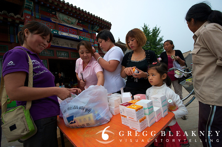 Groups of women arrive on bicycles to buy cosmetics in stage 3's finish host town, Yongning - Stage Three, 162km, Shangyu island to Yongning Town via Thirteen Ming Tombs Reservoir - 2011 Tour of Beijing Scouting Photos