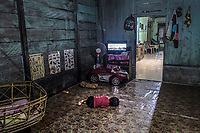 Three year old Putra Marjono lies on the floor watching TV, one of the benefits of the Bajau's new settled lifestyle, in his family's home in the stilt village of Kabalutan.