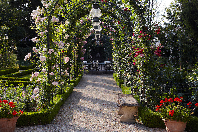 Pink roses create a floral tunnel over a gravel path leading to a tranquil seating area