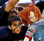 Young Raider fan watches action as his father hangs Chucky doll to intimidate Buccaneers coach Jon Gruden on Sunday, September 26, 2004, in Oakland, California. The Raiders defeated the Buccaneers 30-20.
