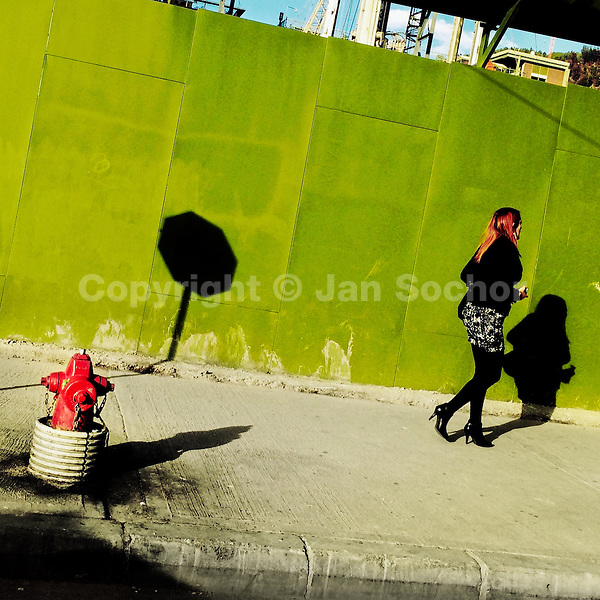 A Colombian woman walks down the sidewalk, passing by a hydrant in front of the construction site in the center of Bogotá, Colombia, 16 February 2016.