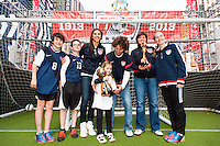U.S. women national team midfielder Carli Lloyd, former women's national team players Michelle Akers, and April Heinrichs pose with fans with the World Cup trophies during the centennial celebration of U. S. Soccer at Times Square in New York, NY, on April 04, 2013.